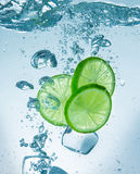Limes with water splash and ice cubes Stock Image
