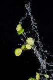Limes with water splashes on black background Royalty Free Stock Image