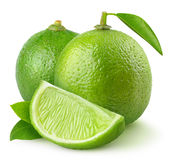 Limes on white. Isolated limes. Two whole lime fruits with leaves and a piece isolated on white background Stock Photo