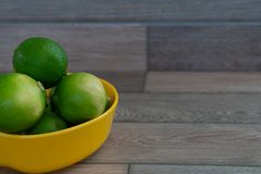 Limes in the yellow bowl stock photography