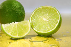 Limes on yellow surface Stock Photos