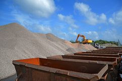Limestone. Hill limestone with shipping containers in the foreground with blue sky and clouds background - excavator and truck stock photo
