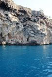 Limestone above turquoise sea. A limestone cliff abutts the turquoise blue ocean water below Stock Images