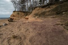 Limestone beach at the Baltic Sea with beautiful sand pattern and vivid red and orange color - Tourist writings on the. Walls and rocks and sand - Cloudy sky stock photos
