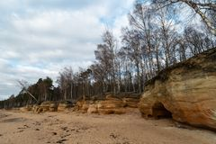 Limestone beach at the Baltic Sea with beautiful sand pattern and vivid red and orange color - Tourist writings on the. Walls and rocks and sand - Cloudy sky stock image