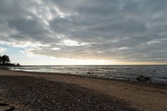 Limestone beach at the Baltic Sea with beautiful sand pattern and vivid red and orange color - Tourist writings on the. Walls and rocks and sand - Cloudy sky stock photography
