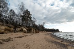 Limestone beach at the Baltic Sea with beautiful sand pattern and vivid red and orange color - Tourist writings on the. Walls and rocks and sand - Cloudy sky royalty free stock photos