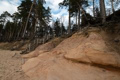 Limestone beach at the Baltic Sea with beautiful sand pattern and vivid red and orange color - Tourist writings on the. Walls and rocks and sand - Cloudy sky royalty free stock images