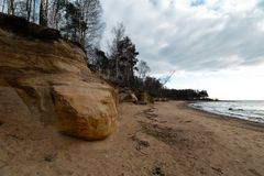 Limestone beach at the Baltic Sea with beautiful sand pattern and vivid red and orange color - Tourist writings on the royalty free stock photography
