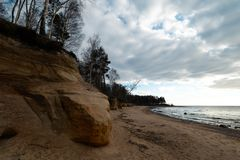 Limestone beach at the Baltic Sea with beautiful sand pattern and vivid red and orange color - Tourist writings on the stock photo