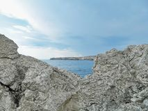 Limestone at Cape Tarkhankut, Crimea. Cloudy sky over limestone formations of the shore at Cape Tarkhankut, Crimea. Large Atlesh cliffs are seen on the horizon stock photos