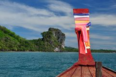 Limestone cliff viewed from a traditional Thai boat. View of limestone cliff of Koh Libong from a traditional Thai long-tail boat. Bow of the boat is decorated stock photo