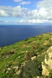 Limestone cliff walls of the Dingli Cliffs in Malta. Summer view of the cumulus clouds building over the warm Mediterranean Sea in Spring.  Fields and stone Stock Photography