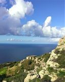 Limestone cliff walls of the Dingli Cliffs in Malta. Summer view of the cumulus clouds building over the warm Mediterranean Sea in Spring.  A ruin perches on the Royalty Free Stock Photos