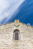 Limestone facade of ancient church with window shutter and cross. Shape in wall Stock Image