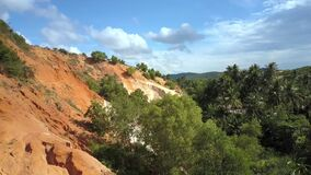 Limestone and Green Jungles against Sky Panorama. Wonderful panoramic view old limestone colored with red clay and green jungles against blue sky with clouds stock video