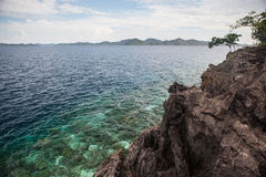 Limestone Island and Fringing Reef. A coral reef grows near a rugged limestone island in Raja Ampat, Indonesia. This region is known to harbor an extraordinary Royalty Free Stock Photography
