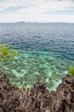 Limestone Island and Reef Scenery. A rugged limestone island is fringed by a healthy reef in Raja Ampat, Indonesia. This region is known to harbor an Royalty Free Stock Photos
