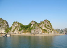 Limestone island rock in the sea bay near fish farm stock photography