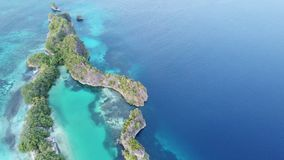 Aerial View of Amazing Island and Lagoon in Raja Ampat. A limestone island surrounds a shallow lagoon in Raja Ampat, Indonesia. This remote, tropical region is stock video
