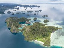 Limestone Islands Aerial in Raja Ampat. The limestone islands found in Raja Ampat rise from calm, blue seas in a remote part of eastern Indonesia. This beautiful royalty free stock photo