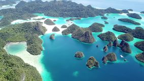 Aerial of Beautiful Islands in Wayag, Raja Ampat. The limestone islands found in Wayag, Raja Ampat, Indonesia, are surrounded by healthy coral reefs. This remote stock video footage