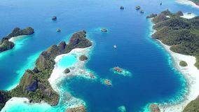 Aerial of Tropical Islands in Wayag, Raja Ampat. The limestone islands found in Wayag, Raja Ampat, Indonesia, are surrounded by healthy coral reefs. This remote stock footage