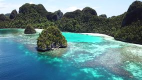 Aerial of Reefs and Islands in Wayag, Raja Ampat. The limestone islands found in Wayag, Raja Ampat, Indonesia, are surrounded by healthy coral reefs. This remote stock video footage