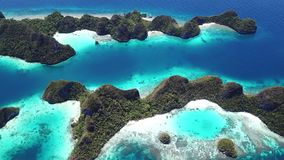 Aerial of Reefs and Islands in Raja Ampat. The limestone islands found in Wayag, Raja Ampat, Indonesia, are surrounded by healthy coral reefs. This remote stock footage