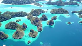 Aerial Footage of Beautiful Limestone Islands in Raja Ampat. Limestone islands rise from a gorgeous, tropical lagoon in Wayag, Raja Ampat, Indonesia. This unique stock video