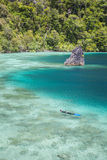 Limestone Islands and Snorkeler in Raja Ampat. A remote lagoon is surrounded by limestone islands in Raja Ampat, Indonesia. This region is within the Coral Stock Photography