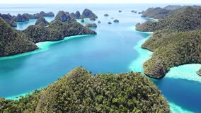 Aerial View of Wayag Islands in Raja Ampat. Limestone islands surround a calm lagoon in Wayag, Raja Ampat, Indonesia. This tropical region is part of the Coral stock footage