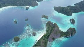 Limestone Islands and Tropical Lagoon in Wayag, Raja Ampat. The gorgeous limestone islands of Wayag, Raja Ampat, are surrounded by shallow coral reefs. This stock video