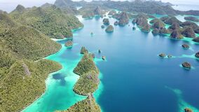 Aerial View of Tropical Islands in Wayag, Raja Ampat. The limestone islands of Wayag in Raja Ampat, Indonesia, are surrounded by healthy coral reefs. This remote stock video