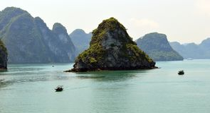 Ha Long Bay Limestone karsts with fishing boats in the near and  middle distance. Limestone karsts with fishing boats in the near and middle distance  - popular Royalty Free Stock Image