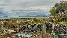 Limestone landscape seen from a farm with a hill and the sea in the background. In the Burren, geosite and geopark, Wild Atlantic Way, spring day in County royalty free stock images