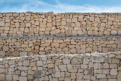 Limestone layered, rough dry stone wall, under a blue sky. Stock Images