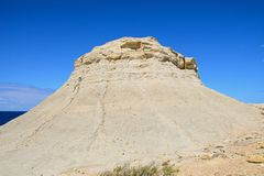 Limestone mound at Marsalforn, Gozo. Limestone mound along the coastline against a blue sky, Redoubt, Marsalforn, Gozo, Malta, Europe Royalty Free Stock Images
