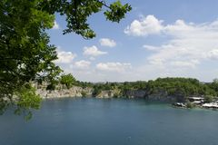 Limestone quarry lake with deep blue water Royalty Free Stock Photography