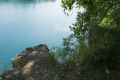 Limestone quarry lake with deep blue water Royalty Free Stock Photos