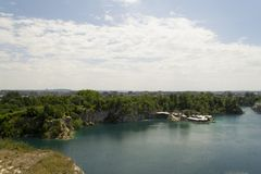 Limestone quarry lake with deep blue water Royalty Free Stock Photo