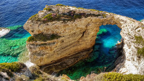 Limestone Rock Arch. Unique towering limestone rock and its thin arch. Paxi island, Greece Stock Image