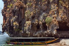 Limestone rock, boat on beach island in andaman sea. Traditional old thai long-tail boat on beach island in andaman sea, cave limestone rock, Phuket, Krabi, Khao Stock Images