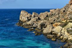 Blue Grotto bay, Mediterranean seacoast, Malta. Limestone rocks and mediterranean seacoast at popular tourist attraction Blue Grotto on a sunny day Stock Photography