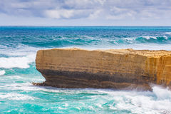 Limestone rocky outcrop reaching out into big ocean waves Stock Image