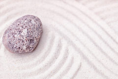 A limestone stone in the fine sand of the zen garden Royalty Free Stock Photos