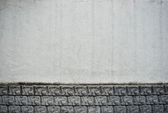 Limestone wall with stains. Grungy white limestone wall with spots and ceramic ornament in the bottom Royalty Free Stock Image