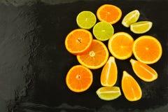 Limette, arance e limoni su fondo nero, spazio della copia Immagini Stock Libere da Diritti