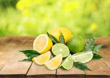 Limette e limoni freschi sulla tavola di legno più Immagini Stock