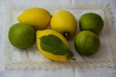 Limette e limoni su una tovaglia fotografia stock
